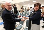 Carson City Library Deputy Director Tammy Westergard presents a check to Mike Jackson, president of Micromanipulator, following a ceremony launching the Carson City School District Foundation at Carson High School, in Carson City, Nev., on Wednesday, Feb. 18, 2015. <br /> Photo by Cathleen Allison