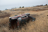 An old, rusty abandoned car lays on its side in a farm field north of Rudyard, Montana, USA.