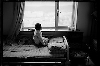 A Tibetan girl sits in front of a window after a cleft palate operation organized by Smile Angel Foundation at a hospital in Xining, Qinghai province, China, August 2013. (Names withheld for privacy)