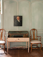 Two gilded chairs stand either side of a wood table with a distressed finish. A portrait painting hangs on the turquoise painted wall behind.