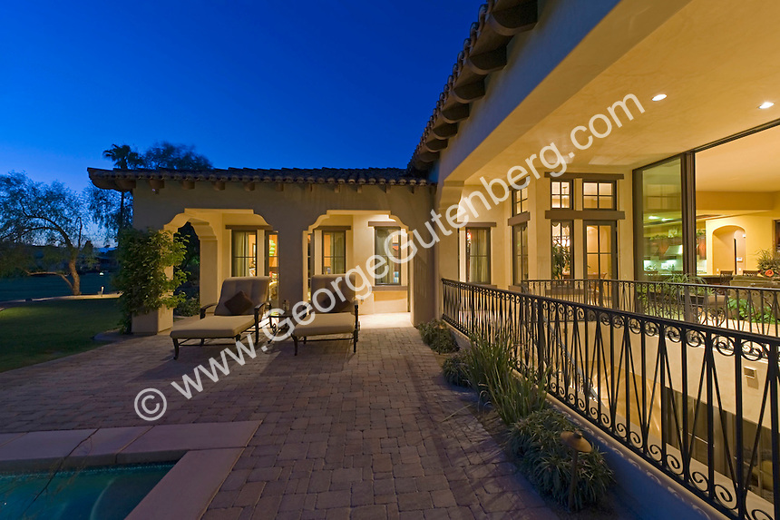 Wrought iron fence leads around patio area by pool