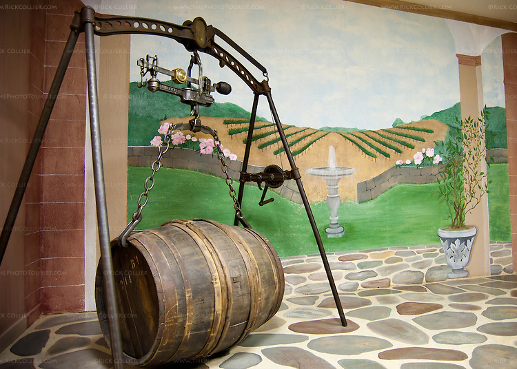 The basement of White Hall Vineyards is dominated by the barrel room.  Outside the barrel room, the foyer features a decoratively painted wall and antique barrel scale.