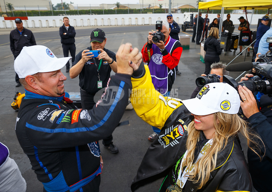 Nov 12, 2017; Pomona, CA, USA; NHRA funny car driver Robert Hight celebrates with top fuel teammate Brittany Force after both clinched the 2017 Nworld championships in their classes during the Auto Club Finals at Auto Club Raceway at Pomona. Mandatory Credit: Mark J. Rebilas-USA TODAY Sports