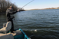 NWA Democrat-Gazette/FLIP PUTTHOFF <br /> Jon Stein, fisheries biologist with the Arkansas Game and Fish Commission, catches a black bass Feb. 17 2017 at Swepco Lake west of Gentry. Water is drawn from the lake in the process of making electricity at the Flint Creek Power Plant, then discharged back into the lake at a temperature of about 100 degrees. That keeps water temperature warm all winter.