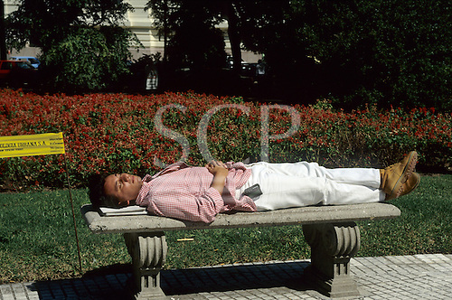 Buenos Aires, Argentina. Man lying down to rest on a concrete park bench with a sign 'Ecologia Urbana'.