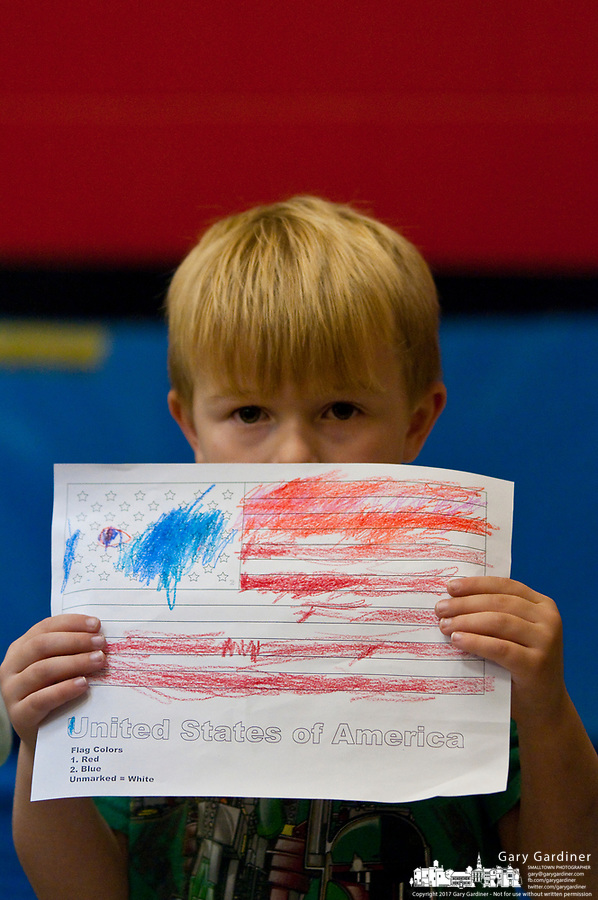 A young boy holds a paper flag he created for observance of Veterans Day at Cherrington Elementary in Westerville, Ohio. The students gathered in the auditorium to listen to two U.S.Army soldiers talks about their experiences and presented gifts to the two men.
