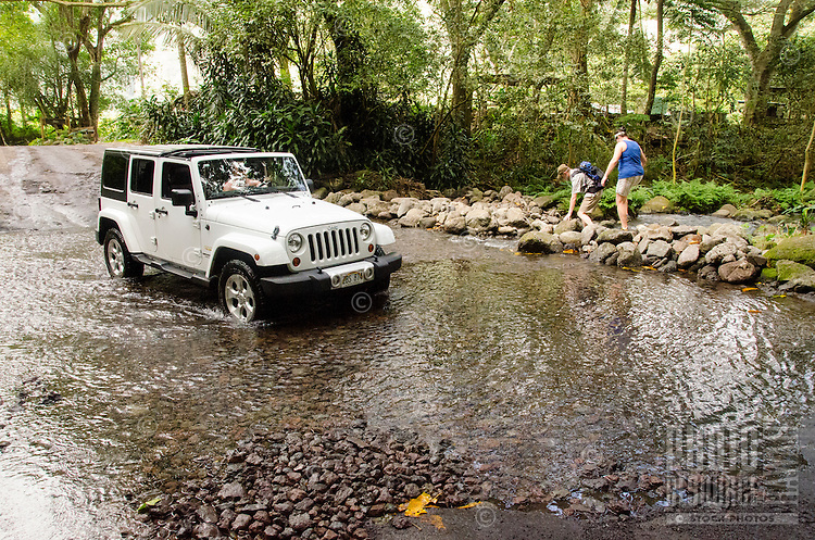 Hikers with a Jeep driving over a small river bed in the back of Waipi'o Valley, Hamakua District, Big Island.