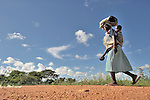 Baby on her back, a woman walks along a road in Thundira, a village in northern Malawi.