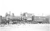 Fireman's-side view of D&amp;RGW locomotive #302 stored at Alamosa with cab boarded up and bell missing.<br /> D&amp;RGW  probably Alamosa, CO  1937-1939