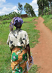 Community Health Worker Marie Chantal walking into her village,  Batamuliza Hururiro near Rukumo Health Center, Rwanda.....