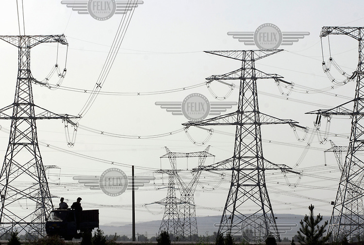 A farm vehicle passes under high voltage electricity towers. Power plants in China's rural north supply over two thirds of Beijing's electricity and suffer environmental pollution and even local brownouts to guarantee the capital's power demand.