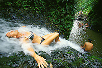 Woman lying in stream of  jungle waterfall, Maunawili Trail, Kailua, Oahu. Hawaii