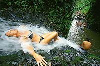 Woman lying in stream of  jungle waterfall, Maunawili Trail, Kailua, Oahu. Hawaii