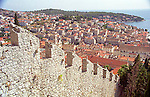 Hilltop view of the Croatian Island town of Hvar and a section of its old castle wall.