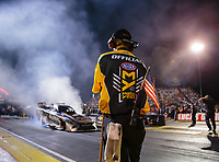 Aug 31, 2018; Clermont, IN, USA; A member of the NHRA safety safari starting line crew wears an American flag in his back pocket as funny car driver Shawn Langdon does a burnout during qualifying for the US Nationals at Lucas Oil Raceway. Mandatory Credit: Mark J. Rebilas-USA TODAY Sports