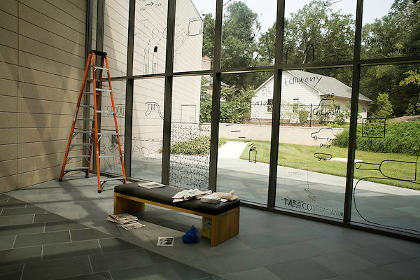 August 24, 2007. Durham, NC..Romanian artists Dan and Lia Perjovschi at the Nasher Museum of Art at Duke University, where their joint exhibition is to open on August 31, 2007.. Dan Perjovschi's work in progress. The newspapers are used for inspiration for the window drawings.