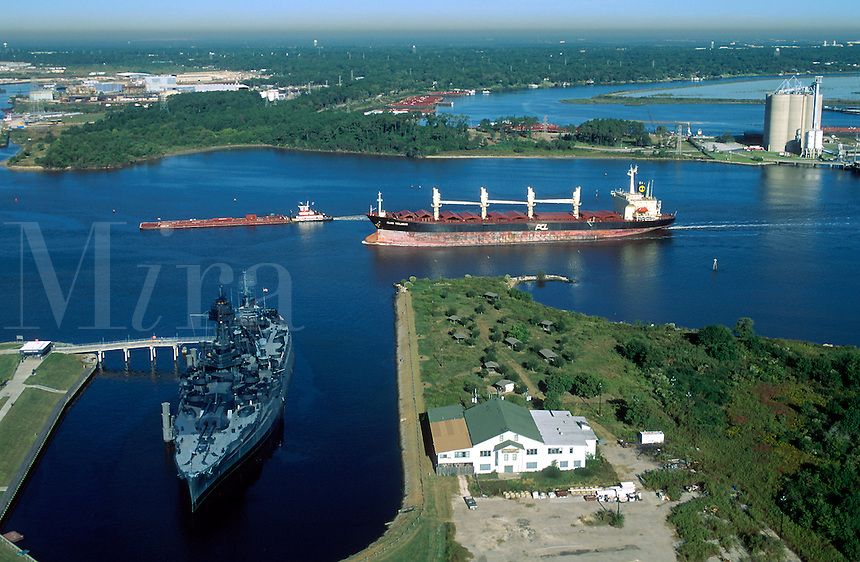 Aerial view of the Houston ship channel as a cargo ship and barge move past the Battleship Texas and Battleground State Park. Houston, Texas.