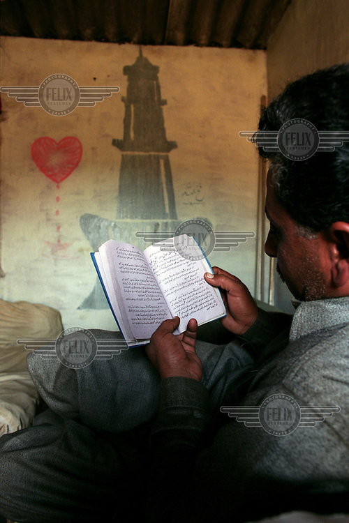 A worker reads from the Holy Koran (Qu'ran) at the Gaddani ship-breaking yard.