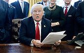 United States President Donald Trump, flanked by business leaders, holds an executive order establishing regulatory reform officers and task forces in US agencies in the Oval Office of the White House on February 24, 2017 in Washington, DC.<br /> Credit: Olivier Douliery / Pool via CNP