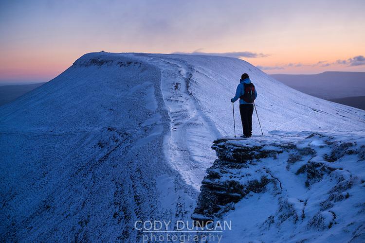 Female hiker looks towards Pen Y Fan at dawn from Corn Du, Brecon Beacons national park, Wales