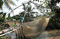 Nguyen Bao Linh is lifting his net with the help of his son. Truong Thanh village, Can Tho province, Mekong delta, Vietnam-2010