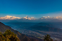 Peaks of the Annapurna Massif of the HImalayas tower above the Pokhara Valley below, seen from Sarangkot, Nepal.