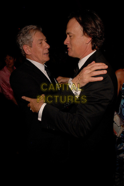 "Sir IAN McKELLEN & TOM HANKS.""The Da Vinci Code"" party at the 59th International Cannes Film Festival, Cannes, France..May 17th, 2006.Ref: FIN.half length black suit jacket hug embrace profile.www.capitalpictures.com.sales@capitalpictures.com.©Steve Finn/Capital Pictures"