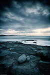 Storm over the sea with rocky forshore