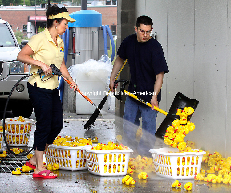 NAUGATUCK CT.-11  JUNE 2010-061110DA02- President of Waterbury Regional Chamber, and   Naugatuck Chamber of Commerce, Lynn Ward and her son Jeffrey Tamizkar of Waterbury volunteer cleaning rubber ducks Friday at at South End Express Car Wash on New Haven Road in Naugatuck. The clean up was followed by Sunday's Fifth Annual Naugatuck River Duck Day and Race. The event was held by the Naugatuck Chamber of Commerce, which raised $40,000 for 85 local nonprofit organizations.