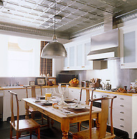 In the kitchen a contemporary take on a traditional coffered ceiling above a pine table surrounded by Chinese chairs