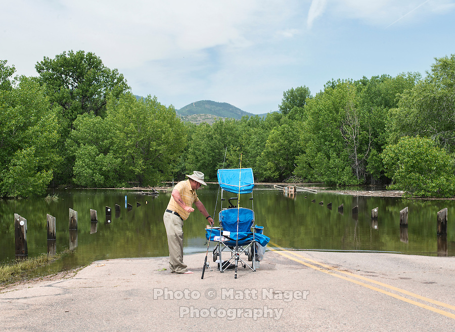 Sam Faus (cq) of, Denver, fishes at a flooded Chatfield Reservoir, in Littleton, Colorado, Monday, June 23, 2015. The reservoir and dam were built by the United States Army Corps of Engineers as a response to a flooding of the South Platte River in 1965. In addition to its primary purpose of flood control, it serves as one of many water supply reservoirs for the city of Denver, Colorado. <br /> <br /> <br /> Photo by Matt Nager
