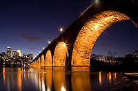 Dramatic view of the Minneapolis skyline at dusk from the famous Stone Arch Bridge and Mississippi river.