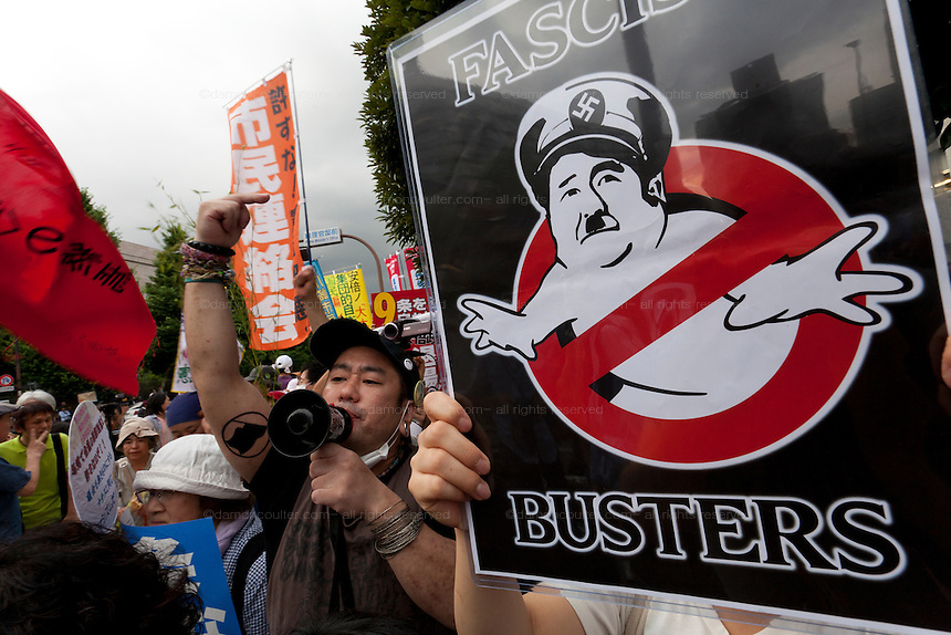 A poster showing Shinzo Abe as a Hitler ghost at a protest against the revision of article 9 of the Japanese Constitution outside the Prime-Minister's house in Kasumigasaki, Tokyo, Japan. Monday June 30th 2014. Over 10,000 people showed their support for Japan's unique peace constitution and called on the government to halt its reinterpretation of Article 9 allowing Collect Self Defence which is expected to become law on July 1st