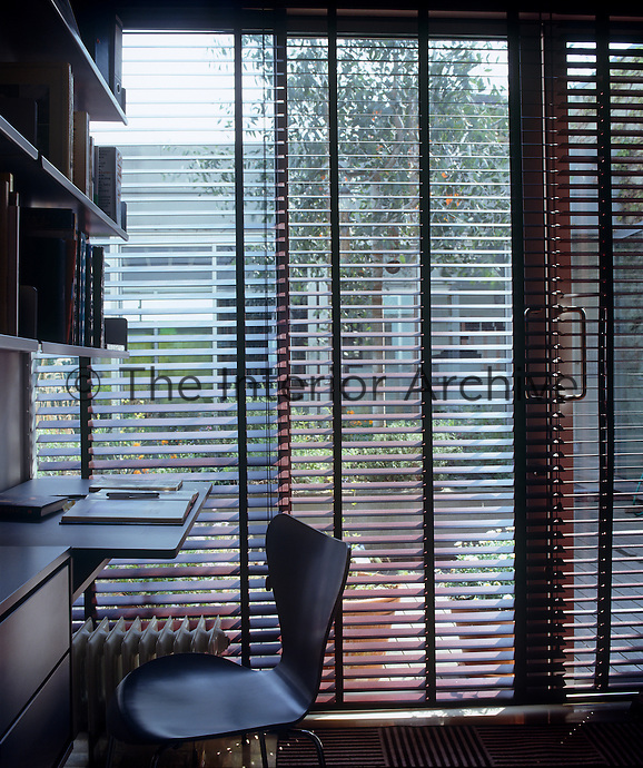 The glass wall of the studio looks out onto the central courtyard and is lined with venetian blinds for privacy