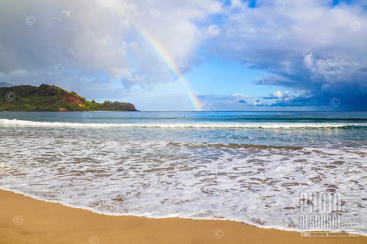 Surfers under a rainbow over Hanalei Bay, as waves roll towards Hanalei Beach, Kaua'i.