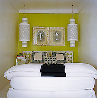 This small bedroom has a yellow wall and is furnished and decorated with pairs of objects