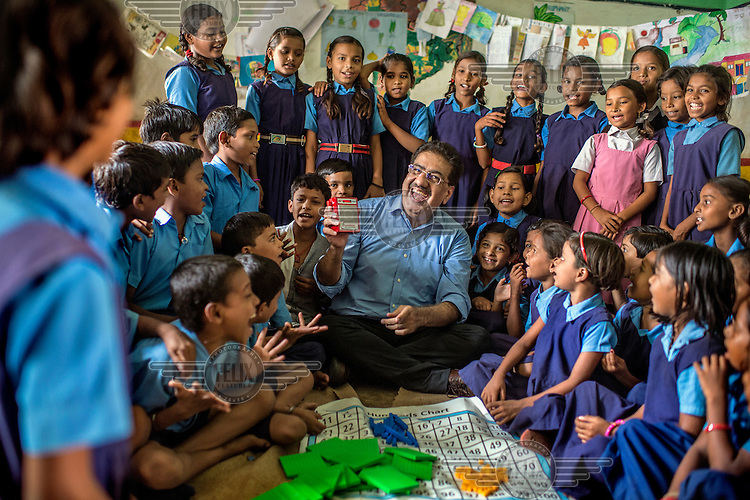 Vineet Nayar, Founder of SAMPARK, spends time with the children of a primary school using a maths kit which their foundation has developed.
