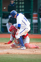 Cornell Big Red catcher Ellis Bitar (24) blocks the plate as Zack Weigel (14) of the Seton Hall Pirates tries to score at The Ripken Experience on February 27, 2015 in Myrtle Beach, South Carolina.  The Pirates defeated the Big Red 3-0.  (Brian Westerholt/Four Seam Images)