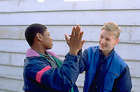 African American and white 14 year old friends slapping high five's.  St Paul Minnesota USA