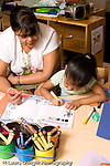 Preschool ages 3-5 female teacher sitting with girl who is drawing horizontal