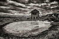 An icy pond in front of a two storey adobe ruin in the ghost town of Guadalupe, New Mexico.