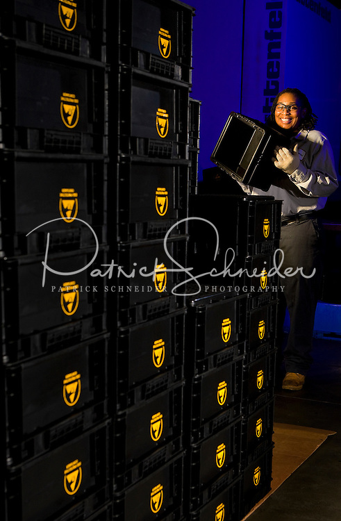 A female worker stacks plastic crates at the SSI Schaefer plastic manufacturing in Charlotte, NC.