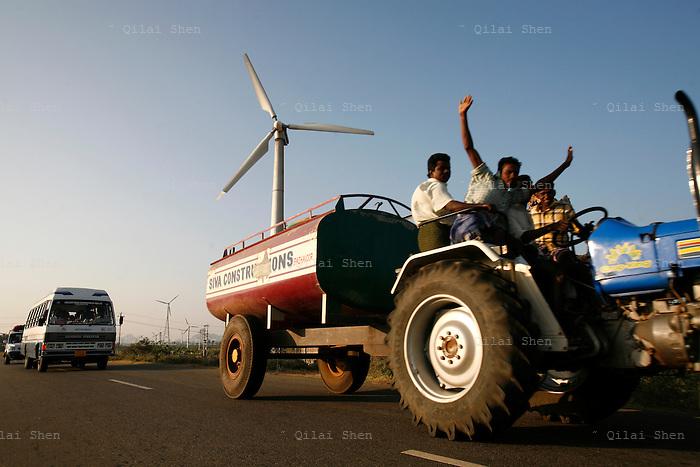 Vehicles drive past wind turbines at Muppanda, near Kanyakumari, Tamil Nadu, India on Sunday, 07 January 2007. Muppanda is the largest wind farm in Asia.