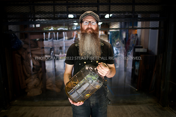 10/13/2011--Seattle, WA, USA..Sound Spirits distiller Kevin Barrans, 32, holds up a pitcher of alcohol on its way to being distilled into vodka...The first craft distillery in Seattle since Prohibition, it's fitting that Sound Spirits sits on 15th Avenue W, just a short amble from downtown and from the water that flows in from the Sound. The company's stylized design sense marries fashionable bottle shapes and a Puget Sound octopus logo and mascot, but what really sets this distillery apart is its flavor profile and the use of Washington malted barley, a grain that comes from the fields of the Palouse, far from Seattle in the state's southeastern corner.. .Opened in September 2010, Sound Spirits is the brain child of distiller (and Boeing engineer) Steven Stone, who continually experimented, tested, researched and tasted a variety of grains before making what could be seen as a curious choice: going with malted barley as a base. There are currently few vodkas and fewer gins that use malted barley as their base grain; for one thing, it's more expensive than other grains. It also adds a large dollop of flavor from the first drop off the still, and many modern vodkas shy away from personality in their taste profiles, going instead for a product that tends to be boringly neutral. But a signature personality and taste is exactly what Stone wanted. And so its Ebb+Flow Vodka ($32) uses 100 percent malted barley, its Ebb+Flow Gin ($33) uses 50 percent, and its newest product (release date wasn't firm at press time), Sound Spirits Aquavit, a Danish-style aquavit, is also based on malted barley. ..Sound Spirits' devotion to malted barley is only matched by its focus on sustainability, with the spent grain going to feed a local farmer's cow and a continuous loop used to save water during the distilling process. While its signature spirits may be named after a mixture of the tides and the Northwest's laid-back nature, Sound Spirits is anything but laid back when