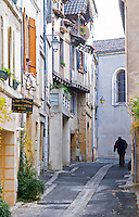 A cobble stone street and old cross beam half timber and stone houses in the Old Town. An old crouched man walking with a walking stick. Bergerac Dordogne France