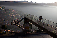 A man walks on top of a bridge early morning on the main highway from La Paz to El Alto.Just 25 years ago it was a small group of houses around La Paz  airport, at an altitude of 12,000 feet. Now El Alto city  has  nearly one million people, surpassing even the capital of Bolivia, and it is the city of Latin America that grew faster .<br /> 	It is also a paradigmatic city of the tubles and traumas of the country. There got refugee thousands of miners that lost  their jobs in 90 &acute;s after the privatization and closure of many mines. The peasants expelled by the lack of land or low prices for their production. Also many who did not want to live in regions where coca  growers and the Army  faced with violence.<br /> 	In short, anyone who did not have anything at all and was looking for a place to survive ended up in El Alto.