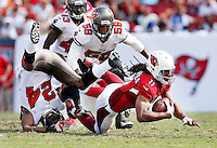 TAMPA, FL - SEPTEMBER 29: Cornerback Darrelle Revis #24 of the Tampa Bay Buccaneers tackles Wide Receiver Larry Fitzgerald #11 during the game against the Arizona Cardinals at Raymond James Stadium on September 29, 2013, in Tampa, Florida. The Buccaneers lost 13-10. (photo by Matt May/Tampa Bay Buccaneers)