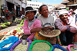 Two women and a man selling white beans at the Analakely market in Antananarivo in Madagascar