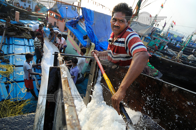 Loading ice into the hold of a fishing boat at Sassoon Docks in Colaba, South Mumbai.