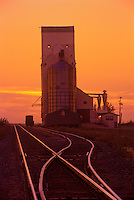 Grain elevator and rail tracks silhouetted against a sunset sky<br /> Wolseley<br /> Saskatchewan<br /> Canada